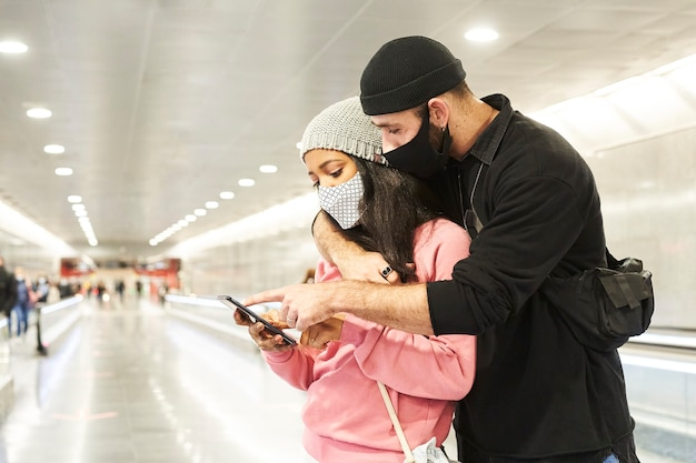 Una giovane coppia interrazziale di amanti con maschere e cappelli di lana in un corridoio della metropolitana