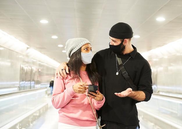 Una giovane coppia interrazziale di innamorati con maschere e cappelli di lana che cammina lungo un corridoio della metropolitana
