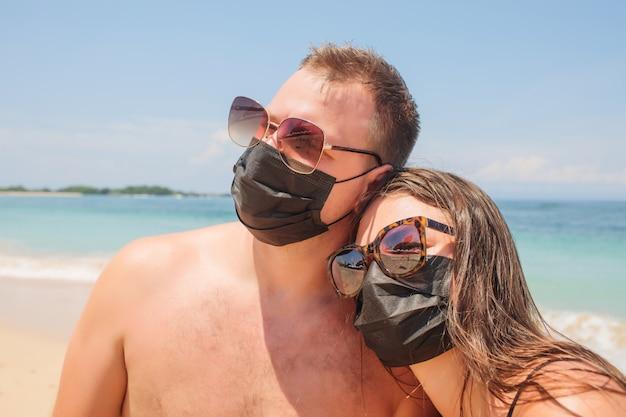 Maschera da portare del respiratore delle giovani coppie interrazziali che fa una pausa la spiaggia proteggendosi dall'infezione virale, virus wuhan, virus della corona durante la vacanza.