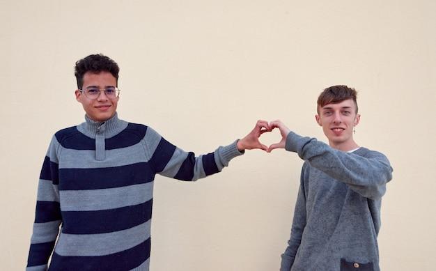 Una giovane coppia gay interrazziale che forma un cuore con le mani isolate su uno sfondo beige
