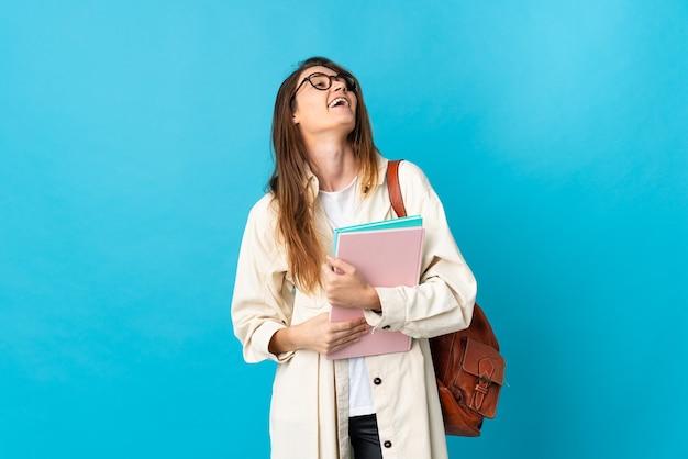 Giovane donna dell'allievo dell'irlanda sopra la risata isolata della parete