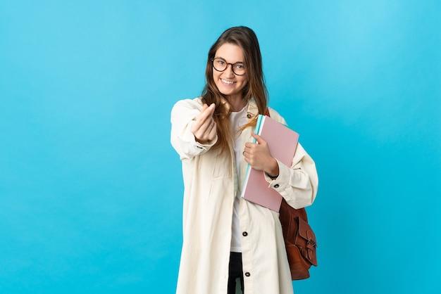 Giovane donna dell'allievo dell'irlanda sopra la parete isolata che fa il gesto dei soldi
