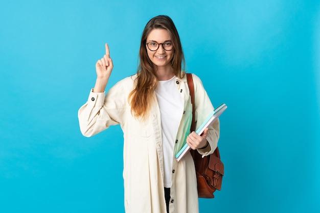 Giovane donna dell'allievo dell'irlanda sopra la parete isolata che indica su una grande idea