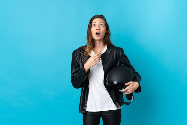 Giovane donna dell'irlanda che tiene un casco del motociclo isolato su priorità bassa blu che osserva in su e con l'espressione sorpresa