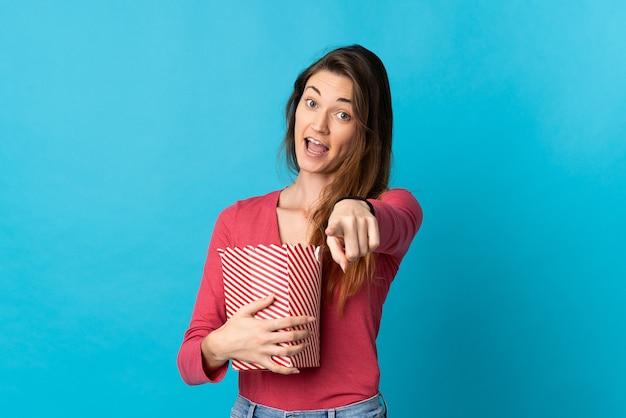 Giovane donna dell'irlanda isolata sulla parete blu che tiene un grande secchio di popcorn mentre indica la parte anteriore