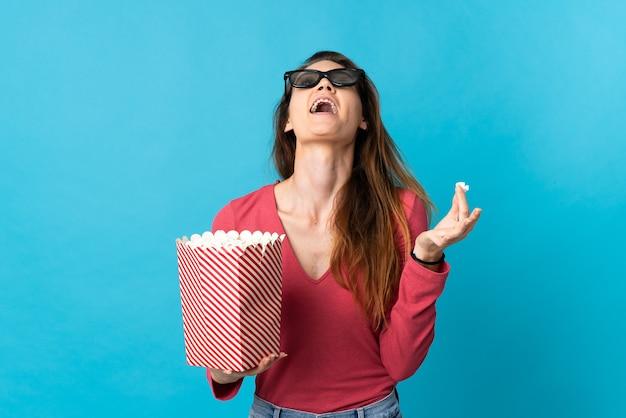 Giovane donna dell'irlanda isolata sulla parete blu con gli occhiali 3d e che tiene un grande secchio di popcorn