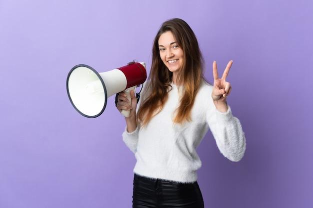 Giovane donna irlanda isolata su sfondo viola in possesso di un megafono e sorridente e mostrando il segno di vittoria
