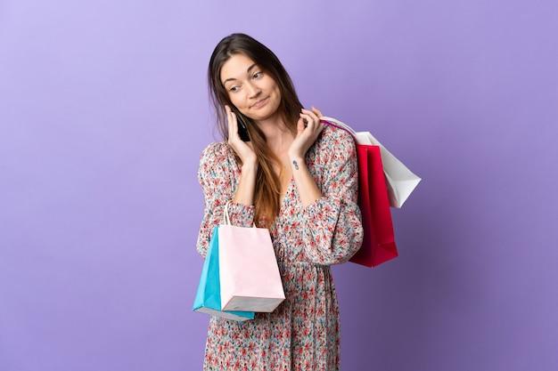 Giovane donna dell'irlanda isolata sulla parete viola che tiene i sacchetti della spesa e chiama un amico con il suo telefono cellulare