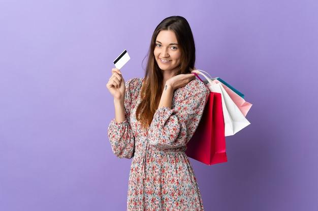 Giovane donna dell'irlanda isolata sulla parete viola che tiene i sacchetti della spesa e una carta di credito