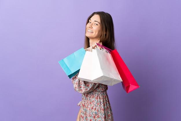 Giovane donna dell'irlanda isolata sul muro viola che tiene i sacchetti della spesa e sorridente