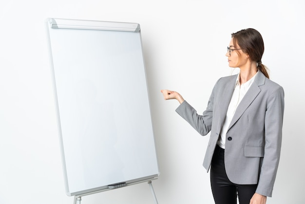 Giovane donna irlanda isolata su sfondo bianco, dando una presentazione sulla lavagna bianca