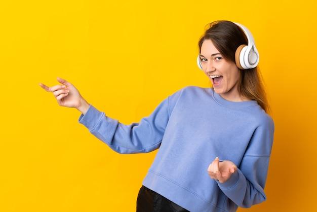 Giovane donna dell'irlanda isolata sulla parete gialla che ascolta la musica e che fa il gesto della chitarra