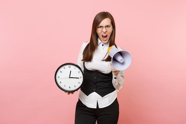 Giovane donna d'affari irritata con gli occhiali che urla tenendo il megafono e la sveglia isolati su sfondo rosa pastello. signora capo. concetto di ricchezza di carriera di successo. copia spazio per la pubblicità.