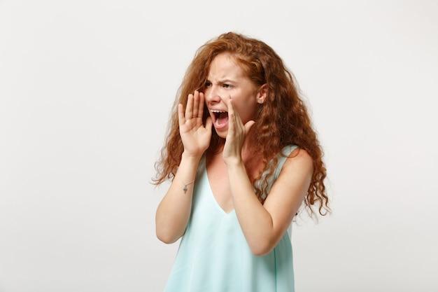 Giovane donna irritata della testarossa in vestiti leggeri casuali che posano isolati su fondo bianco in studio. concetto di stile di vita della gente. mock up copia spazio. guardando da parte urlando con il gesto della mano vicino alla bocca.