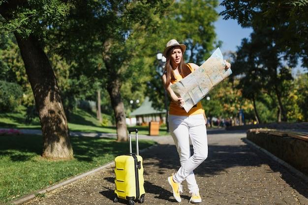 La giovane donna turistica irritata del viaggiatore in vestiti casuali gialli di estate, cappello con la mappa della città della valigia cammina in città all'aperto. ragazza che viaggia all'estero per viaggiare nei fine settimana. stile di vita del viaggio turistico.