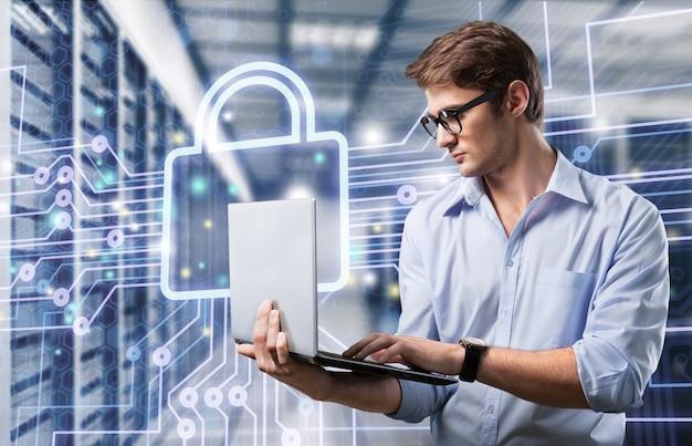 Giovane uomo d'affari ingegnere informatico con laptop in alluminio moderno e sottile nella sala server di rete