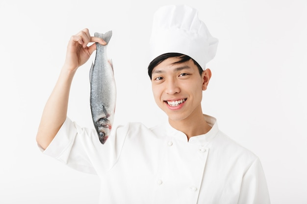 Giovane capo giapponese in uniforme da cuoco bianca e cappello che sorride mentre tiene in mano pesce fresco crudo isolato su un muro bianco