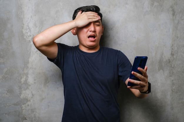 Giovane uomo giapponese che utilizza smartphone stressato con la mano sulla testa, scioccato dalla vergogna e dal viso sorpreso, arrabbiato e frustrato sullo sfondo del muro di cemento. paura e turbamento per errore.