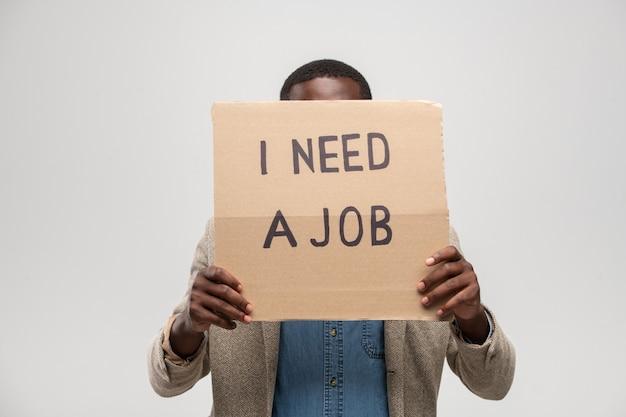 Giovane disoccupato di etnia africana che nasconde il viso dietro un pezzo di cartone dicendo che ha bisogno di un lavoro mentre è in piedi