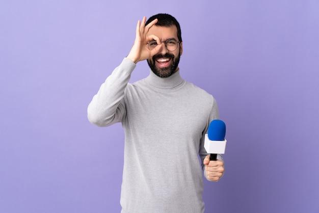 Giovane uomo del giornalista sopra la parete isolata