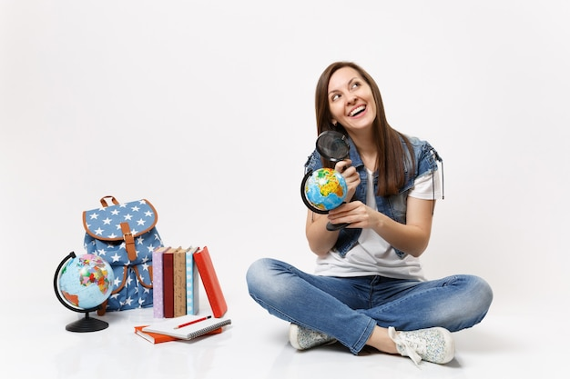 Giovane bella studentessa gioiosa che tiene il globo del mondo e la lente d'ingrandimento che si siedono vicino allo zaino, libri di scuola isolati sul muro bianco