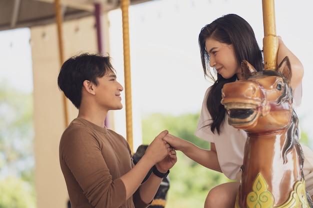 Giovane coppia gioiosa uomo e donna a cavallo al parco divertimenti carousel