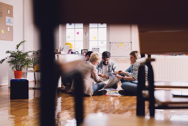 Giovani gioiosi imprenditori creativi seduti sul pavimento dell'ufficio nel cerchio e brainstorming con piacere. il lavoro di squadra e il concetto di solidarietà.