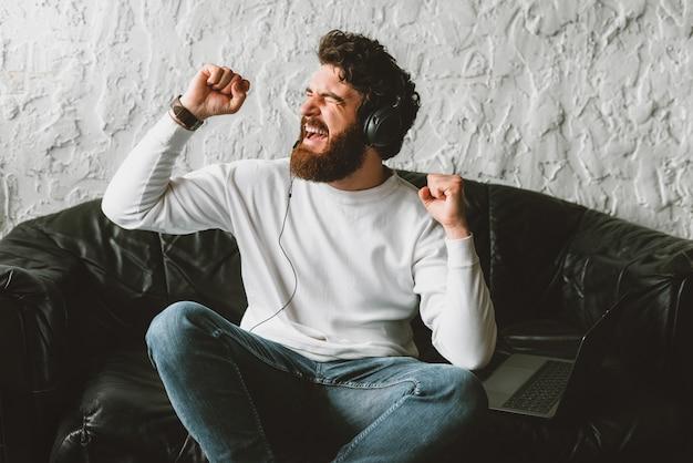 Musica d'ascolto del giovane uomo allegro e rilassarsi sul sofà