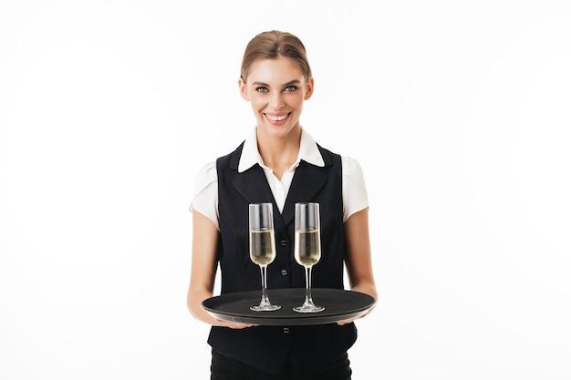 Giovane cameriera gioiosa in uniforme tenendo il vassoio con gli occhiali felicemente