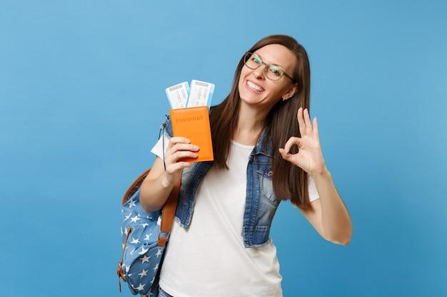 Giovane studentessa gioiosa in bicchieri con zaino in possesso di passaporto, biglietti per la carta d'imbarco e mostrando segno ok isolato su sfondo blu. istruzione in college universitario all'estero. volo aereo.