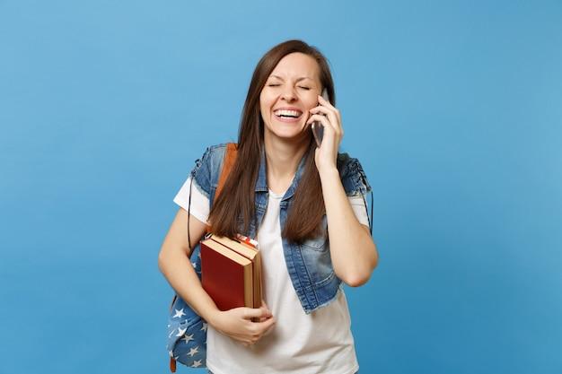 Giovane studentessa allegra con lo zaino che tiene i libri di scuola che parla sul telefono cellulare che conduce una conversazione piacevole isolata su fondo blu. istruzione nel concetto di college universitario di liceo.
