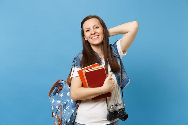 La giovane studentessa allegra con lo zaino e la retro macchina fotografica d'annata sul collo che tiene la mano sulla testa tiene i libri di scuola isolati su fondo blu. istruzione nel concetto di college universitario di liceo.