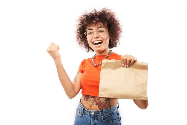 Giovane donna gioiosa con riccioli afro in vestiti arancioni che tengono pacchetto artigianale isolato su sfondo bianco studio, consegna cibo, borsa ecologica, ragazza caucasica kazaka con regalo