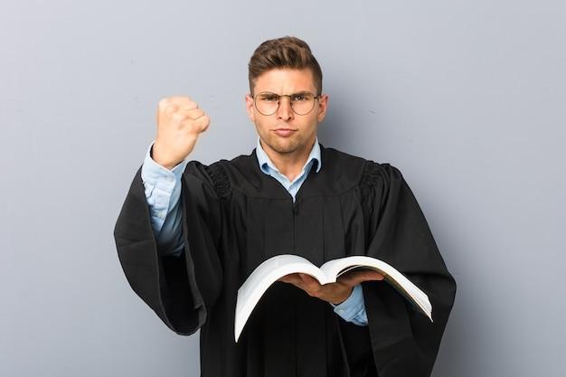 Giovane giurista che tiene un libro che mostra il pugno alla macchina fotografica, espressione facciale aggressiva.