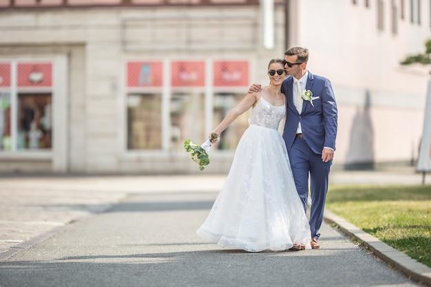 Una giovane coppia appena sposata che cammina felicemente in città in abiti da sposa con un bellissimo bouquet. lo sposo sta baciando la sua sposa.