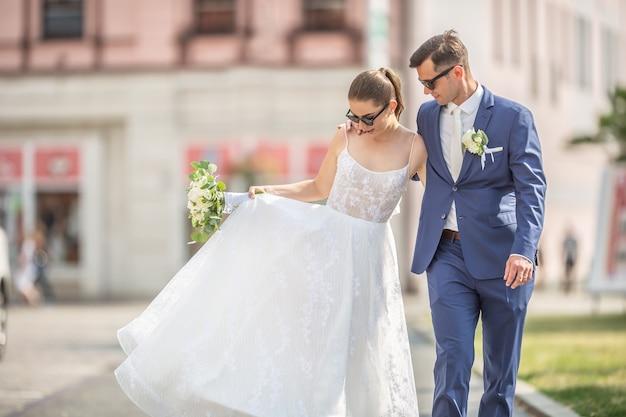 Una giovane coppia appena sposata che cammina felicemente in città in abiti da sposa con un bellissimo bouquet.
