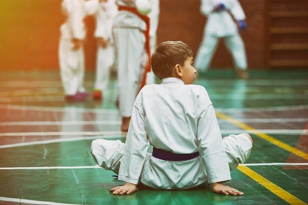 Giovane ragazzo di karatè che si scalda in un kimono