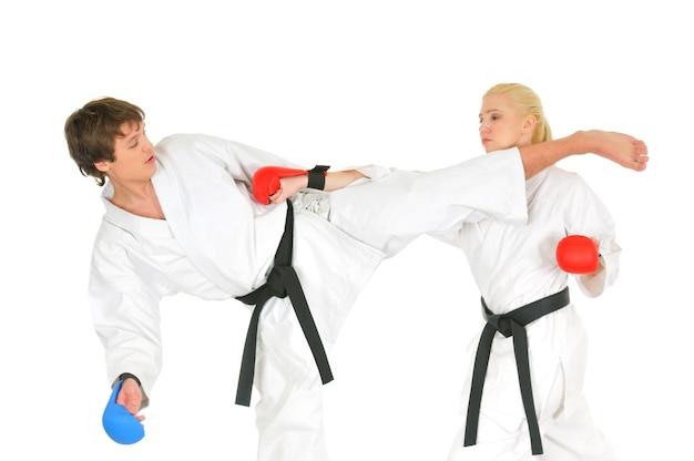 Giovani studenti di karateka in kimono bianco cinture nere in guanti da combattimento si allenano per praticare colpi con calci e mani su sfondo bianco