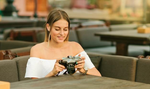 Giovane donna appassionata tiene la vecchia macchina fotografica retrò nelle sue mani mentre è seduto al tavolo in un caffè all'aperto