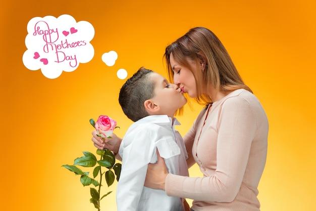 Ragazzino che dà una rosa rossa a sua madre. felice festa della mamma concetto