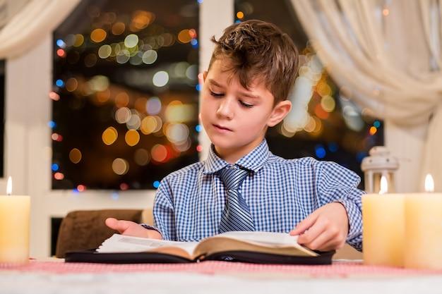 Il ragazzino gira la pagina del libro. libro di lettura del bambino di notte. atmosfera di vacanza tranquilla a casa. mente brillante e pensieri puri.