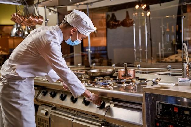 Giovane addetto alla cucina che ruota la manopola del fornello a destra e accende il fuoco su un fornello