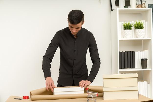 Un giovane coreano in un ufficio confeziona un pacco regalo per la spedizione postale.