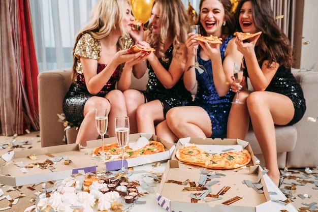 Giovani donne che celebrano la festa di compleanno a casa, mangiano pizza, bevono champagne, si divertono. coriandoli intorno.
