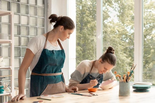 Giovane donna in grembiule in piedi al tavolo e insegnare agli studenti