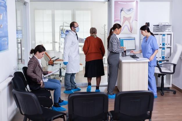 Giovane donna che chiede informazioni compilando un modulo stomatologico mentre i pazienti parlano seduti su una sedia nell'area di attesa. persone che parlano nell'ufficio di reception dell'ortodontista professionale affollato.