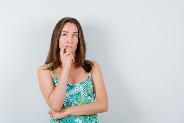 Giovane donna in camicetta in piedi in posa di pensiero e guardando pensieroso, vista frontale.
