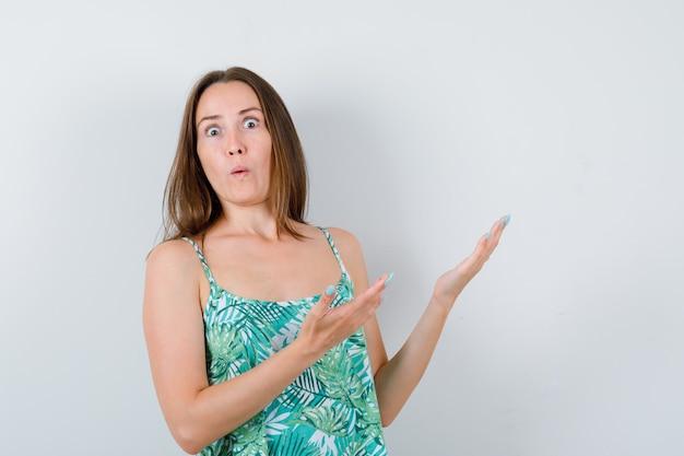 Giovane donna in camicetta che accoglie qualcosa e sembra perplessa, vista frontale.