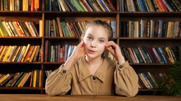 La giovane donna in giacca marrone alza la mano e risponde alle domande