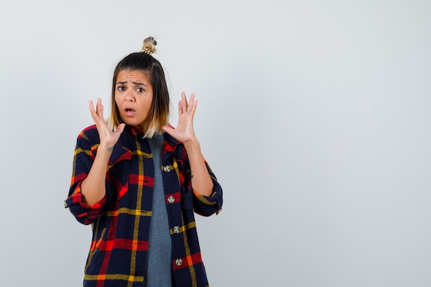 Giovane donna in camicia casual a quadri che tiene i palmi vicino al viso e sembra risentita, vista frontale.